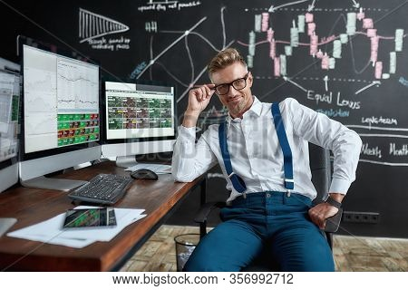 Middle-aged Caucasian Trader In Glasses Looking At Camera While Sitting By Desk In Front Of Computer