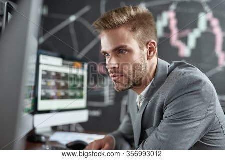 Close Up Portrait Of Successful Trader Looking Focused While Sitting In Front Of Monitors In The Off