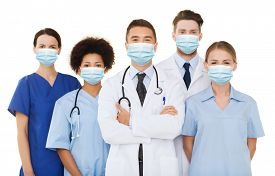 health, medicine and pandemic concept - doctors and nurses wearing protective medical masks on white background