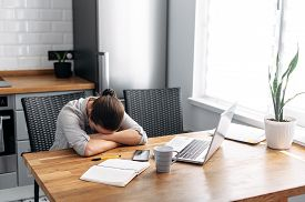 Forced Work From Home. A Young Woman Is Bored Working From Home, She Laid Her Head In Her Hands. Its