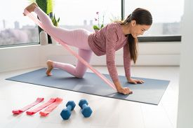 Resistance band fitness at home Asian woman doing leg workout donkey kick floor exercises with strap elastic. Glute muscle activation with kickback for thighs cellulite.