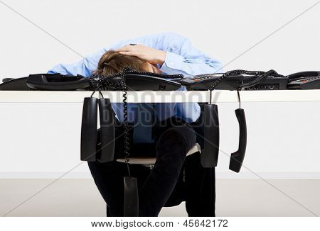 Tired businessman sitting in the office with a bunch of phones on his front