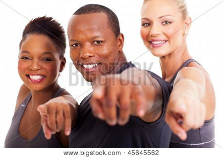 smiling group of gym instructors pointing at the camera on white background