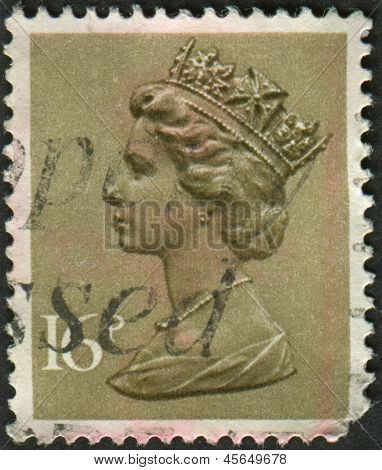 UK-CIRCA 1983: A stamp printed in UK shows image of Elizabeth II is the constitutional monarch of 16 sovereign states known as the Commonwealth realms, in Olive Drab, circa 1983.