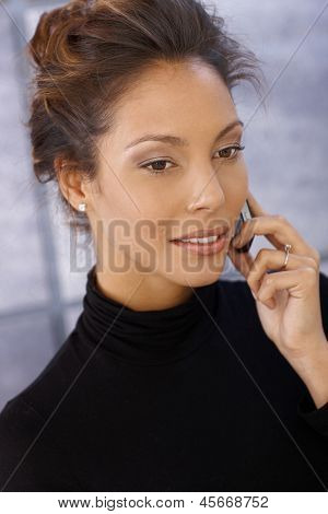 Portrait of attractive afro-american businesswoman on mobile phone in polo-neck sweater.