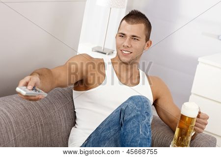 Young sporty guy in undershirt on sofa with beer , using remote control, smiling.