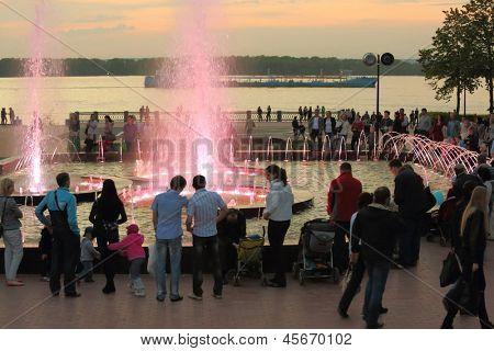 SAMARA - MAY 5: People walk with children near fountain in evening, on May 5, 2012 in Samara, Russia. Fountain was opened in 2011 during the reconstruction of the second phase of the waterfront.