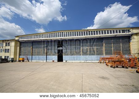 Big old battered aircraft hanger with big gate at sunny summer day. poster