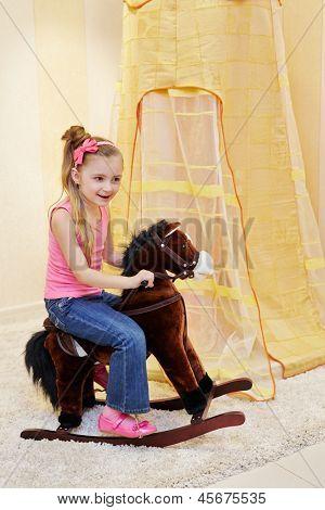Little girl rocks on hobbyhorse in play room