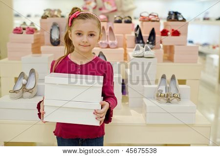 Little girl stands and holds two shoe boxes in shoe store