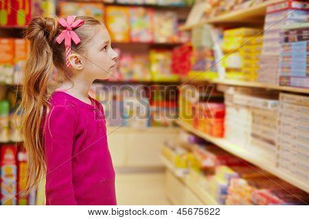 Little girl wonderingly looks on abundance of board games in book department in store