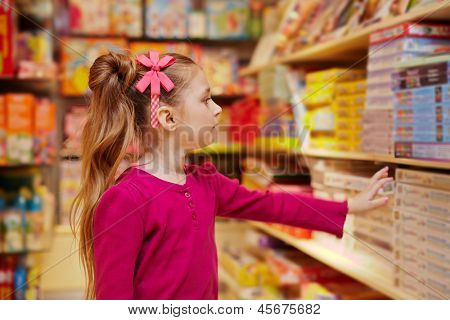Little girl stretches to shelf with table games in book department of store