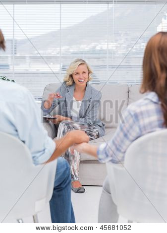 Smiling therapist speaking a couple during therapy session