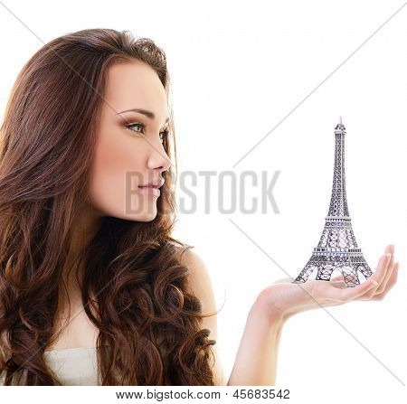 Beautiful girl holding little Eiffel tower, over white
