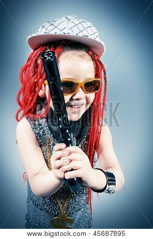 Portrait of a trendy little girl wearing red braids and modern clothes and holding a gun. poster