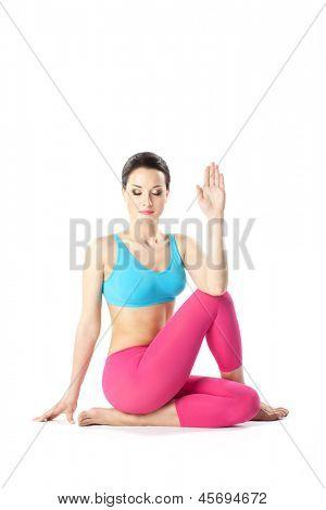 young beautiful yoga posing ardha matsyendrasana on a gray studio background