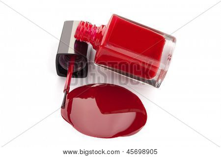 Red nail polish bottle with spilled varnish isolated on white background