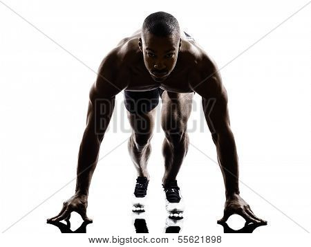 one young african muscular build man on starting blocks silhouette  isolated on white background