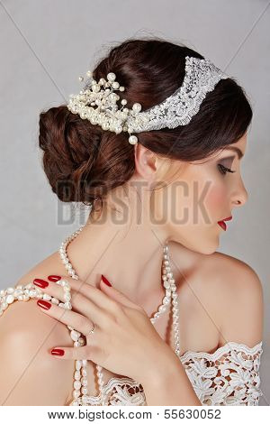 Beautiful young bride with wedding makeup in romantic lace dress on studio background