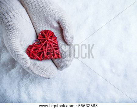 Female hands in white knitted mittens with a entwined vintage romantic red heart on a snow background. Love and St. Valentine concept. poster