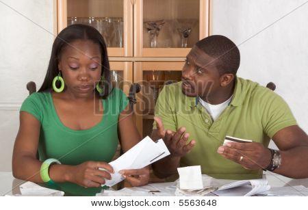 junge ethnischen Couple von Tabelle überwältigt von Rechnungen