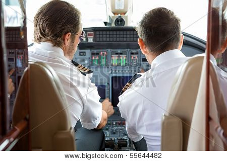 Rear view of pilot and copilot in private jet cockpit
