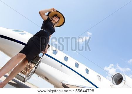 Low angle view of woman in elegant dress standing in front of private jet against sky