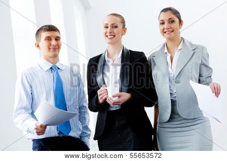 Image of three young businesspeople laughing joyfully