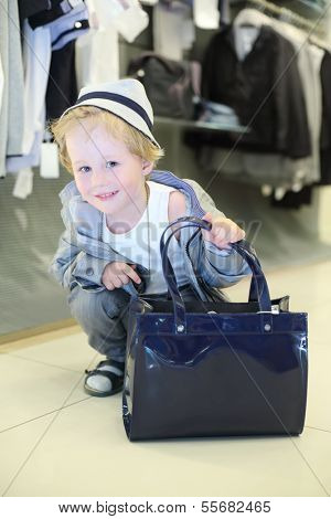 Little boy with bag sits near clothes hangers in children clothing shop.