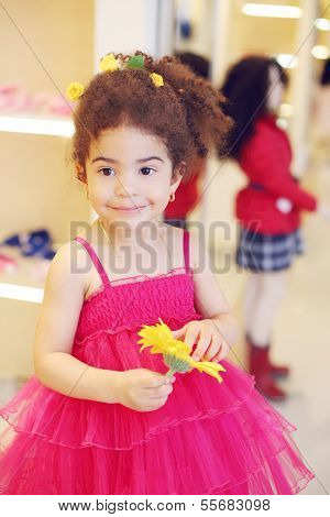 Little girl in pink dress with flower stands and smiles in children store.
