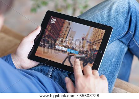 Man Sitting On The Sofa And Holding Ipad With App Linkedin On The Screen