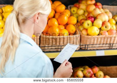 Girl reads shopping list near the heap of fruits lying in the braided baskets in the store