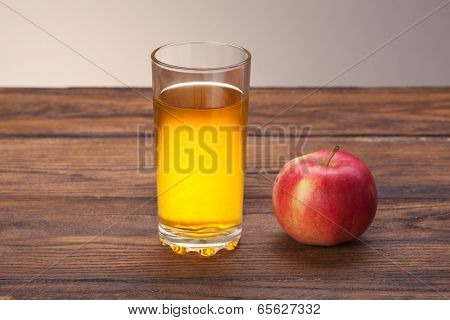 Glass of apple juice and red apple on wooden background
