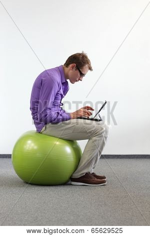 man with tablet on large stability  ball - bad sitting posture