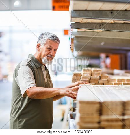 Man buying construction wood in a  DIY store for his DIY home re-modeling project