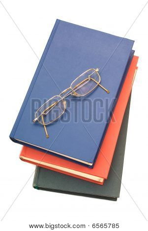 Spectacles and stack of three books