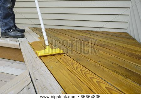Worker Applying Stain to Deck