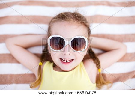 Adorable little girl lying on a beach towel during summer vacation