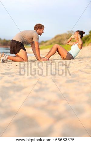 Young fitness couple working out doing situp crunches. Pretty asian fitness woman doing sit ups - caucasian male model helping kneeling happy smiling. Training crossfit on beach sand in sunset