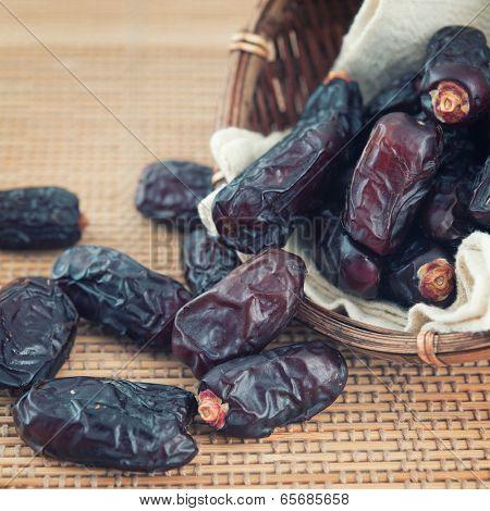 Dried date palm fruits or kurma, ramadan food which bamboo basket.