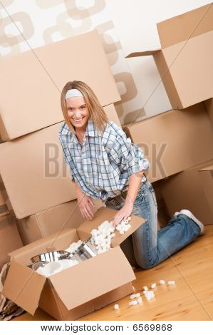 Moving House: Happy Woman Unpacking Box
