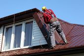 roofer builder worker with pulverizer spraying paint on metal sheet roof poster