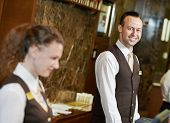 Happy receptionist worker standing at hotel counter poster