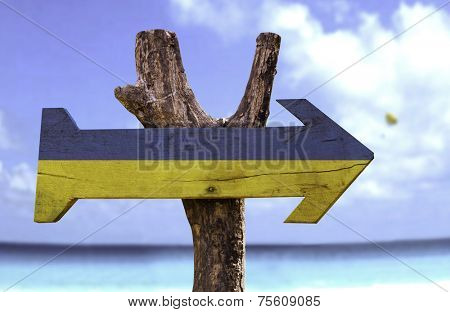 Ukraine wooden sign with a beach on background