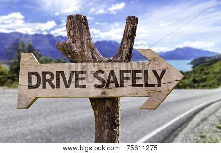 Drive Safely wooden sign with a street background