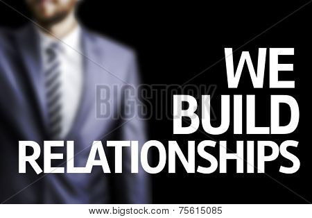 We Build Relationships written on a board with a business man on background