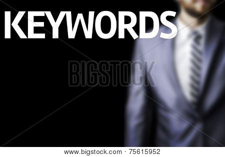 Keywords written on a board with a business man on background