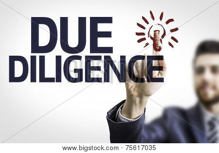 Business man pointing to transparent board with text: Due Diligence