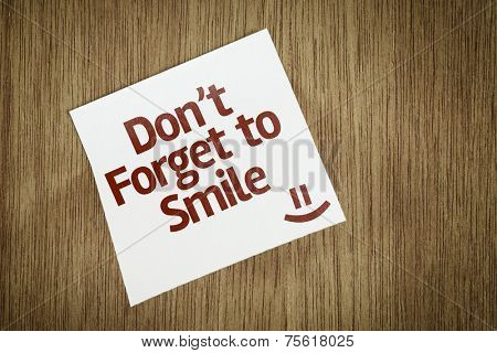 Don't Forget to Smile on Paper Note on texture background