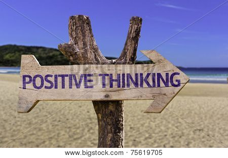 Positive Thinking wooden sign with a beach on background